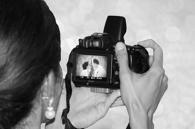 photographer-looking-into-camera-with-image-of -couple