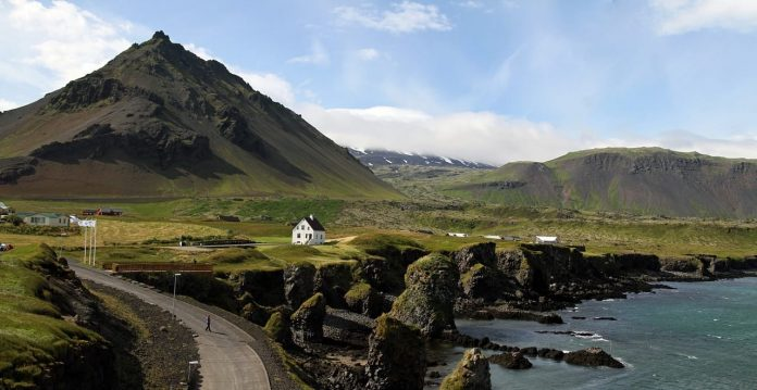 Road in Iceland leading up to a white house overlooking the sea with mountain in the background